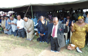 Local leaders, some of them former enemies, bow during prayers for reconciliation.